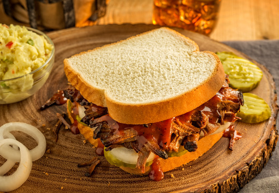 Mrs Baird's BBQ Brisket Sandwich served with pickles and potato salad