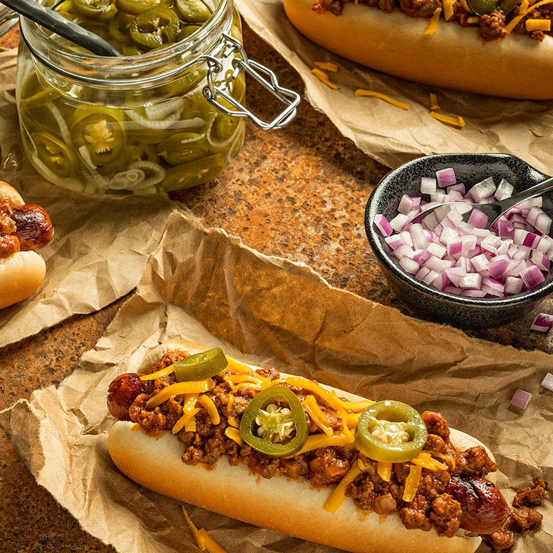 Mrs Baird's Texas Chili Cheese Hot Dog, topped with jalapeños and served with diced red onion on the side